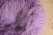 Armchair with a purple extra-long-hair cover