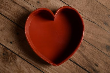 Damaged red heart-shaped rustic bowl