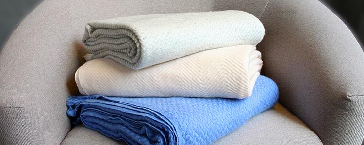 Plaid en cachemire gris, bleu et rose sur un canapé