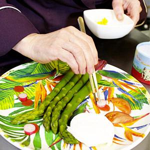 Karin Burton placant ses ingredients dans les assiettes en mélamine colorées des jardins de la comtesse au restaurant Lou Ferri