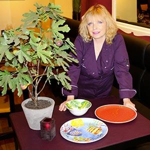 Photo de Karin Burton posant à coté des assiettes en mélamine des jardins de la comtesse au restaurant Lou Ferri